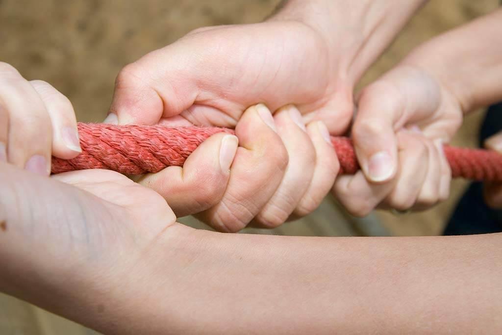 Mehrere Hände ziehen an einem Seil.