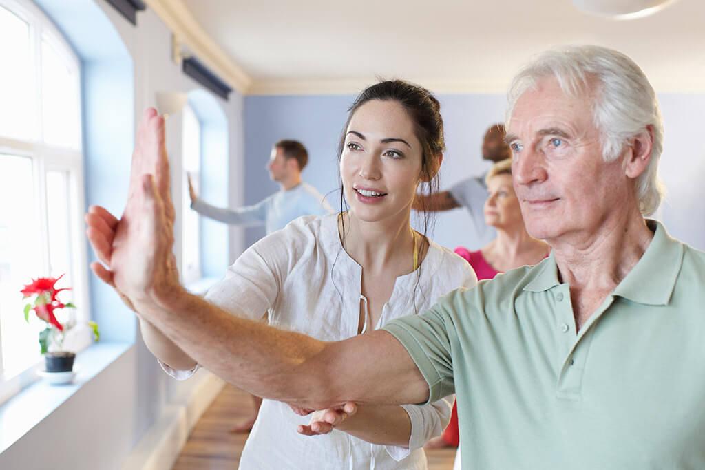 Eine Frau macht Gymnastikübungen mit einem älteren Herrn.