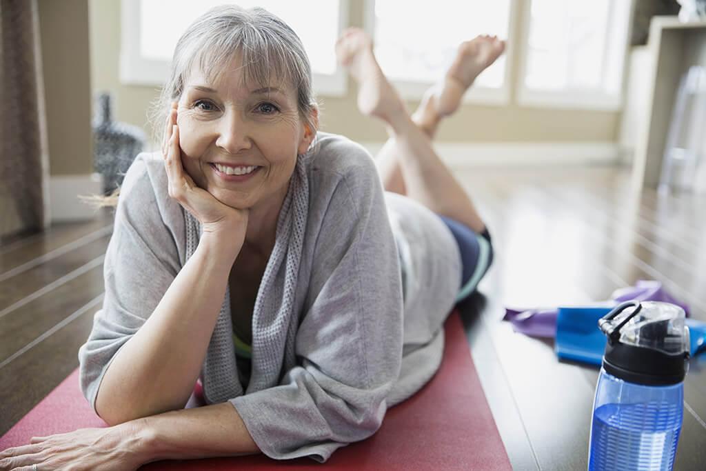 Eine Frau liegt auf einer Yogamatte und lächelt in die Kamera.