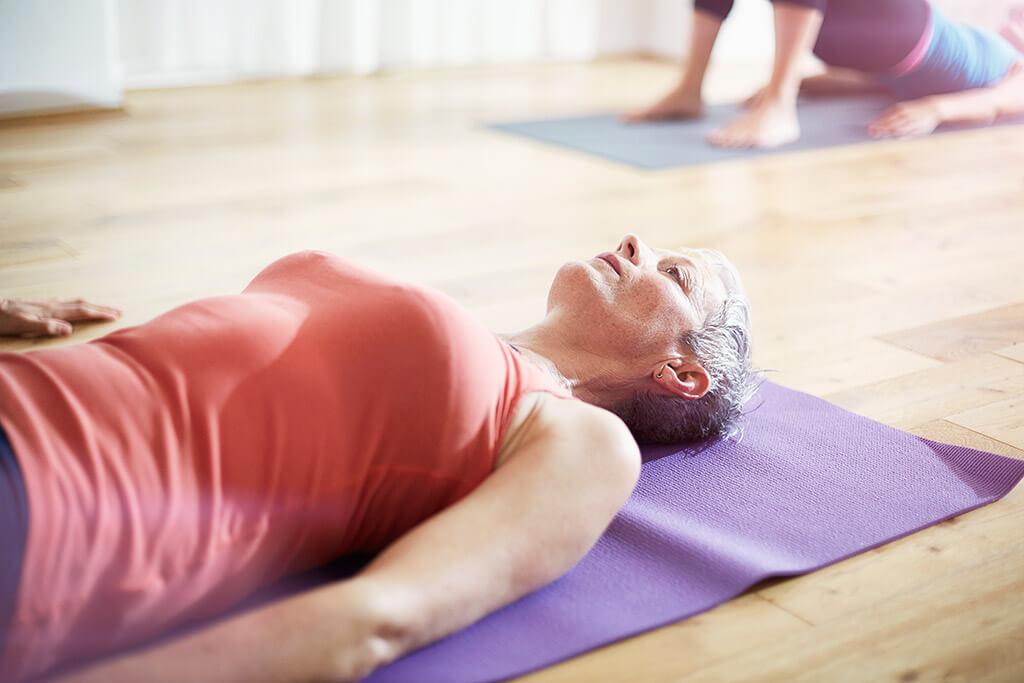 Eine Frau liegt auf einer Yogamatte.