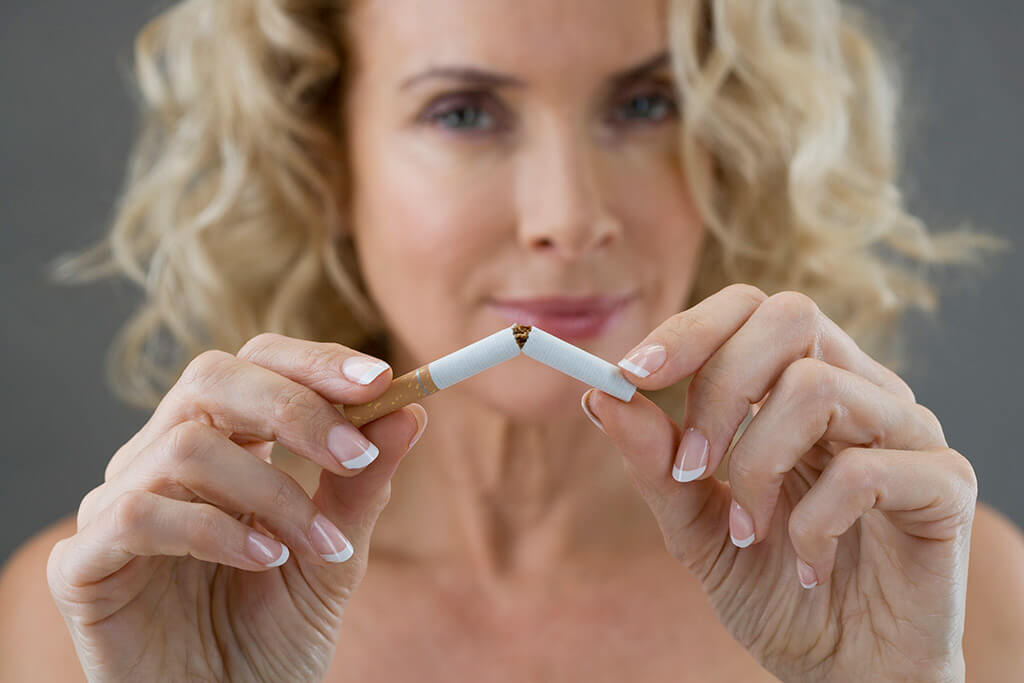 Eine Frau mit blondem Haar zerbricht eine Zigarette.