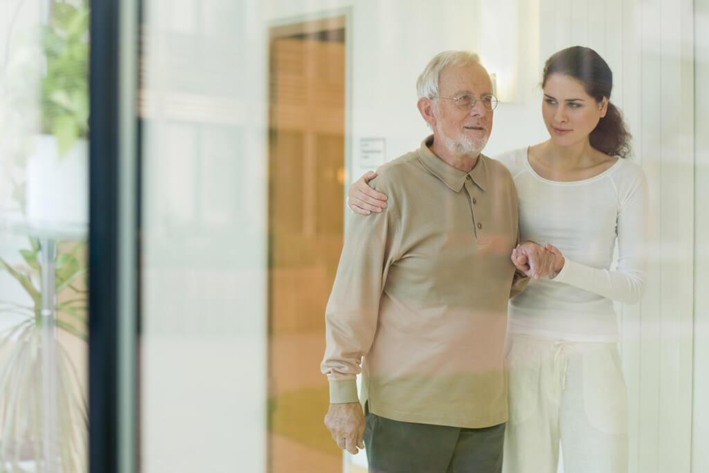 Eine Pflegerin hilft einem älteren Mann beim laufen.