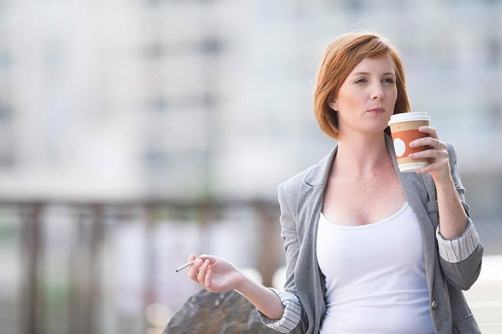 Eine Frau trinkt einen Kaffee und raucht eine Zigarette.