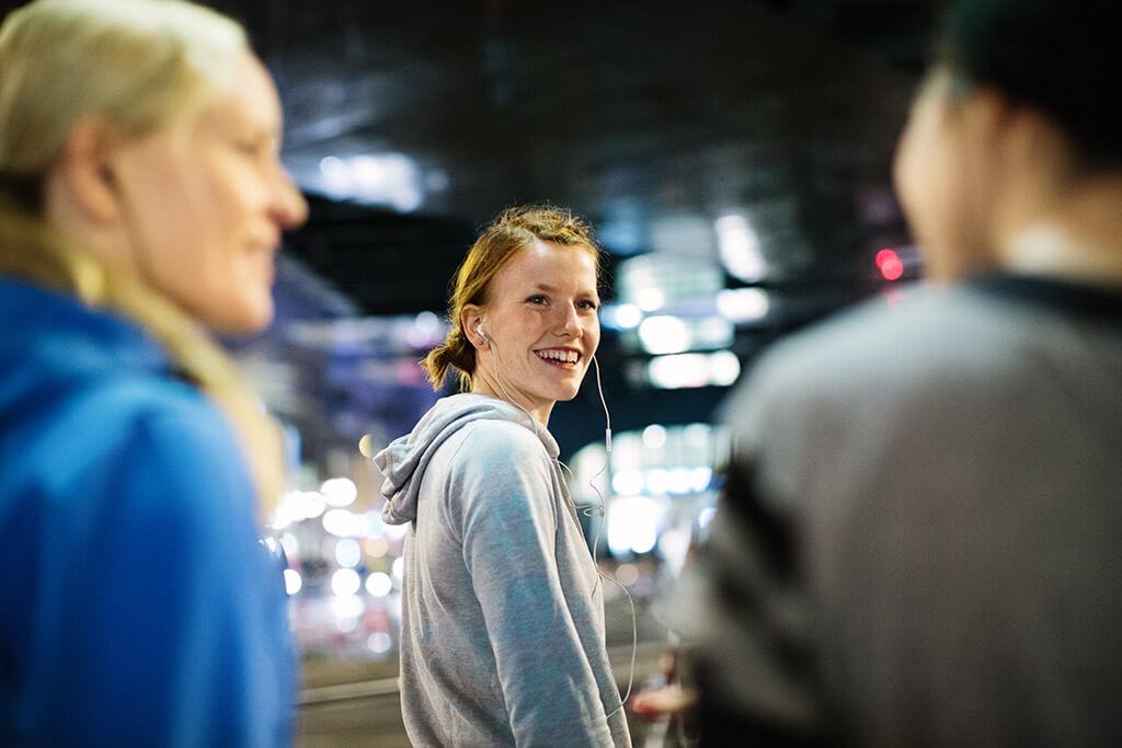 Ein Mädchen mit Kopfhörern lächelt zwei andere Personen an.