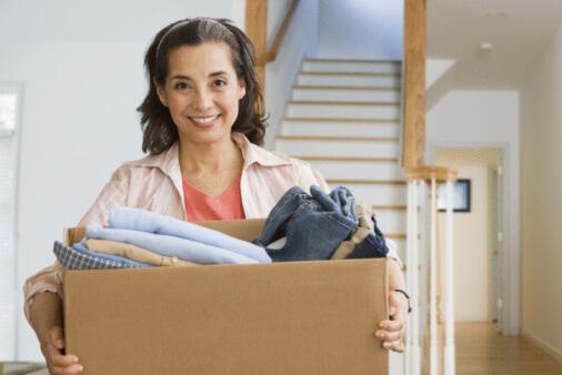 Eine Frau trägt eine Kiste voller Kleidung.