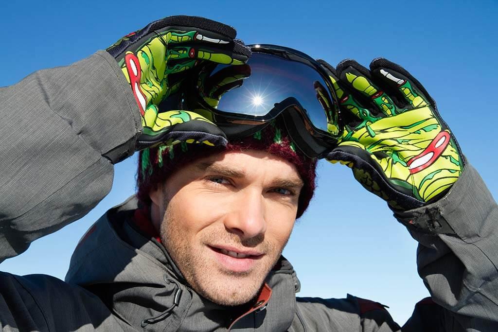 Ein Mann ein Skibekleidung zieht seine Skibrille an.