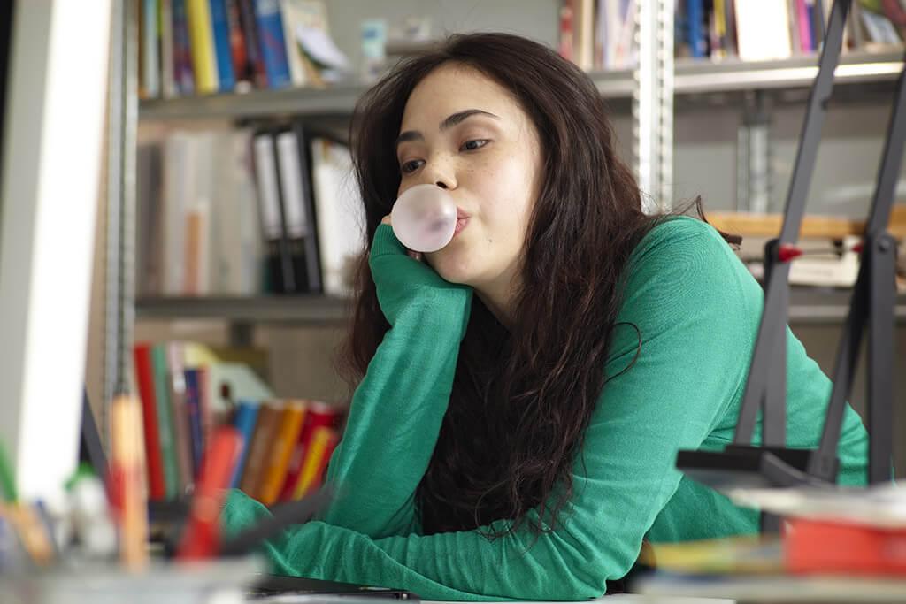 Ein Mädchen in einem grünen Pullover macht eine Kaugummiblase.