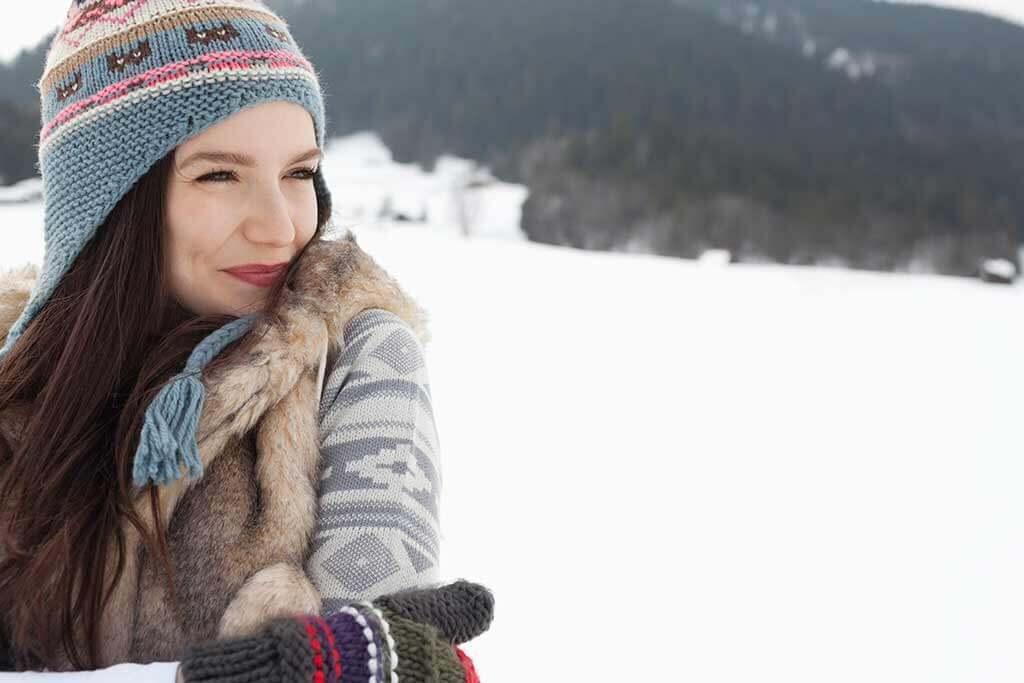 Eine junge Frau in Winterkleidung im Schnee.