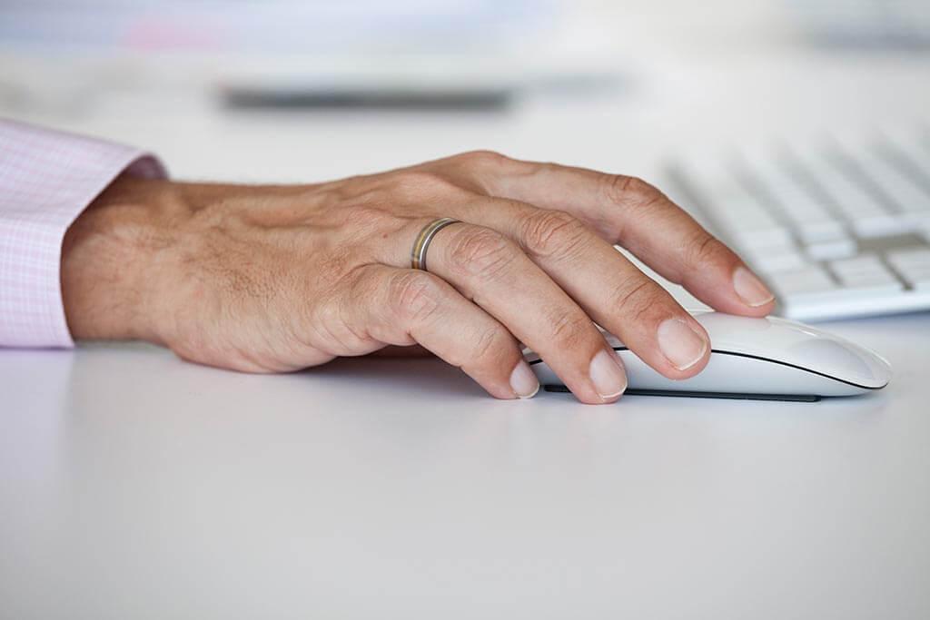 Eine Hand liegt auf einer Computermaus.