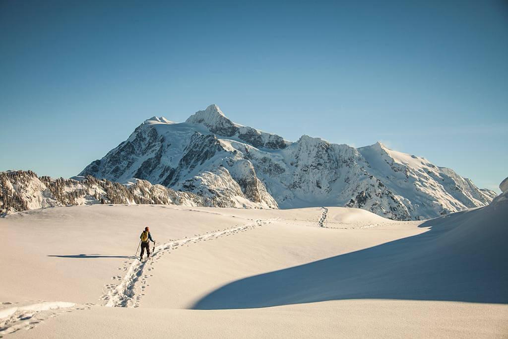 Eine einzelne Person wandert allein durch eine Schneelandschaft.