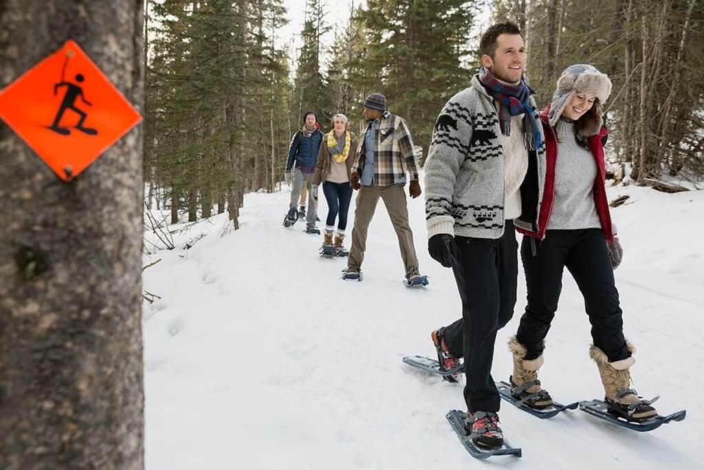 Eine Gruppe junger Menschen macht eine Schneeschuhwanderung.