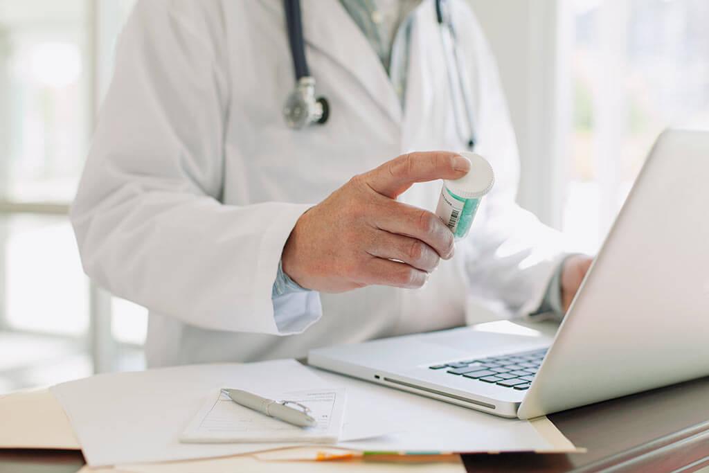 Ein Arzt schaut sich eine Tablettenverpackung an während er am Laptop ist.