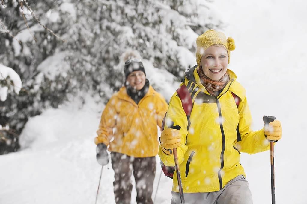 Ein Paar in gelber Kleidung wandern im Schnee.