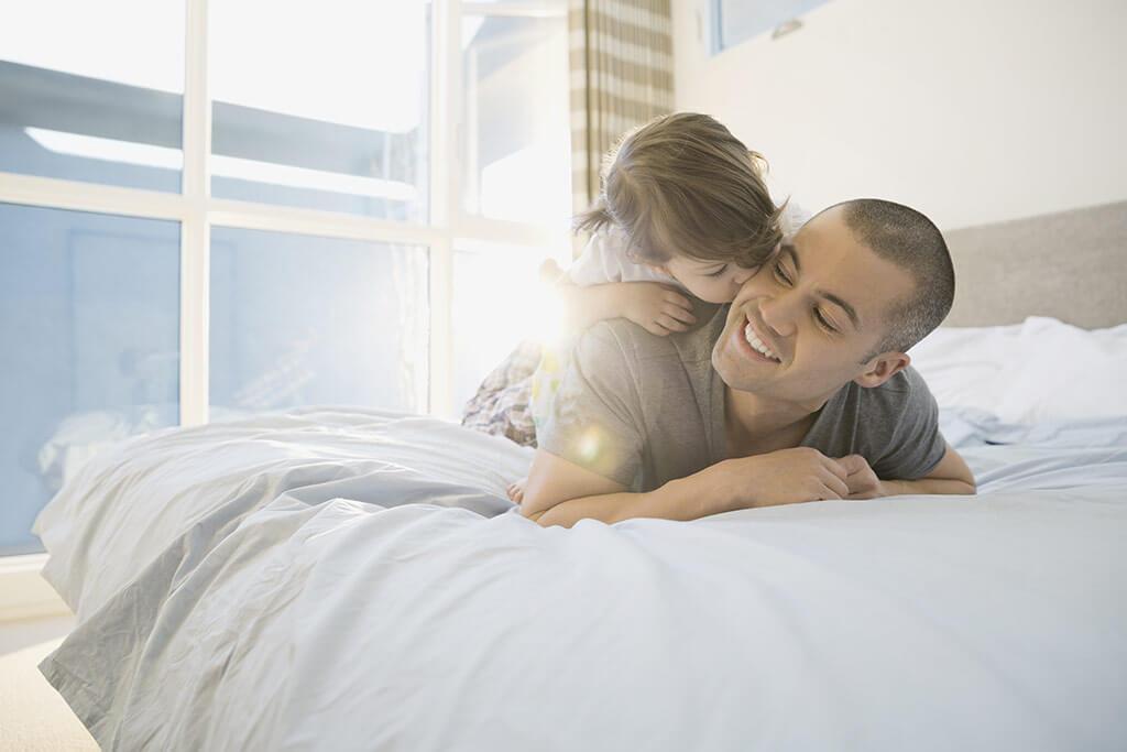 Ein Vater liegt im Bett mit seiner Tochter auf dem Rücken und sie gibt ihm einen Kuss auf die Backe.