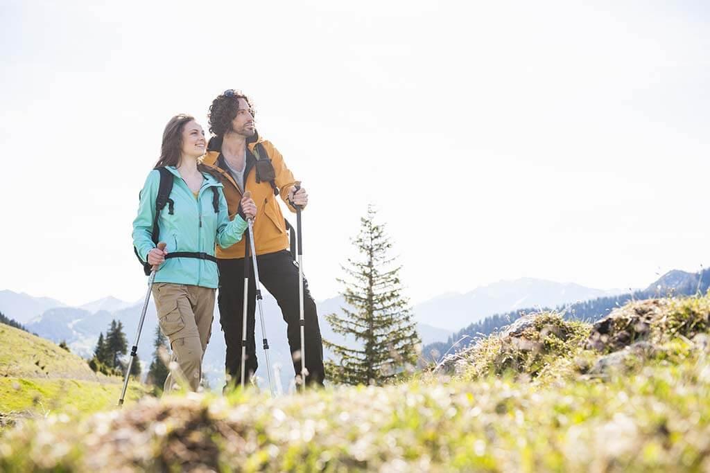 Ein Paar mit Wanderstöcken genießen zusammen die Aussicht.