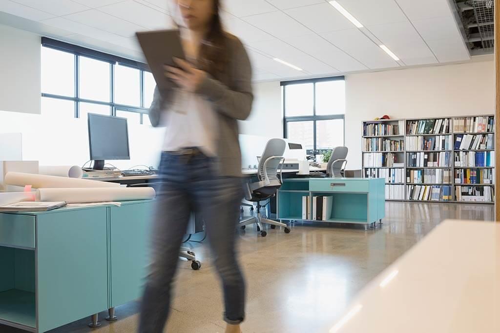 Eine Frau lauft eilig durch ein leeres Büro.