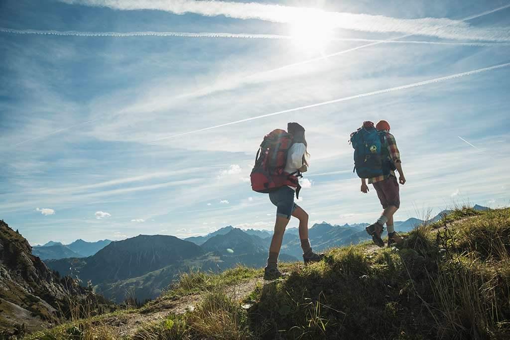 Ein Paar mit Rucksäcken wandert in den Bergen.