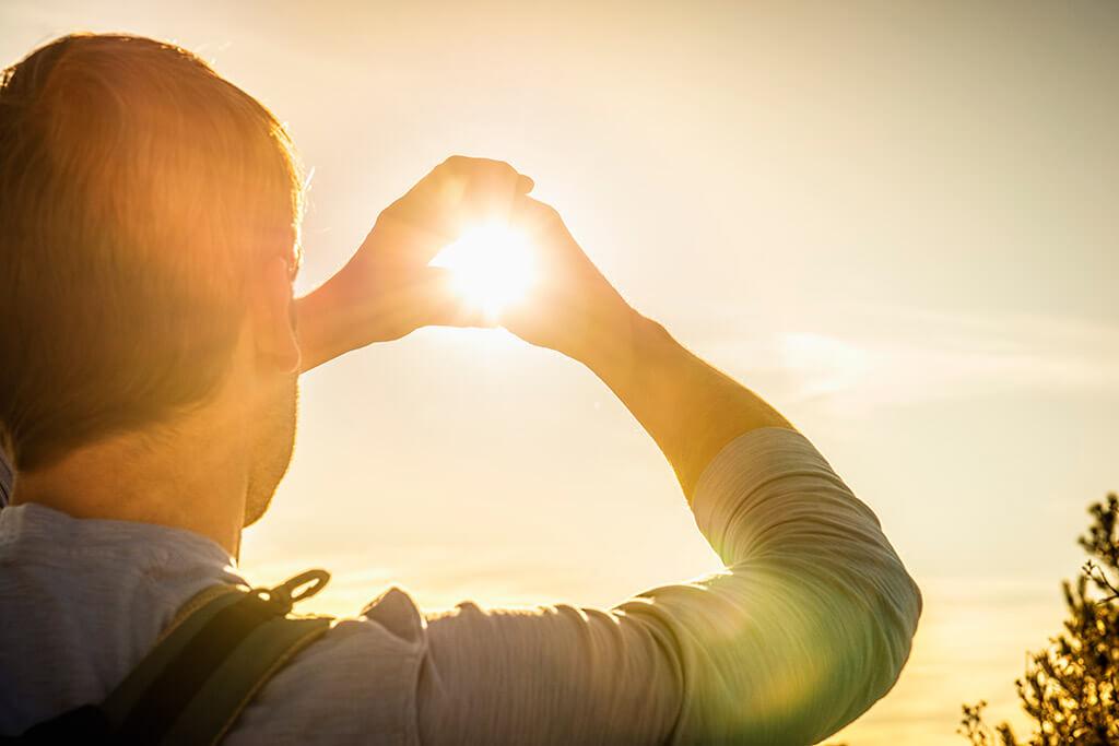 Ein Mann umrahmt die Sonne mit seinen Händen.