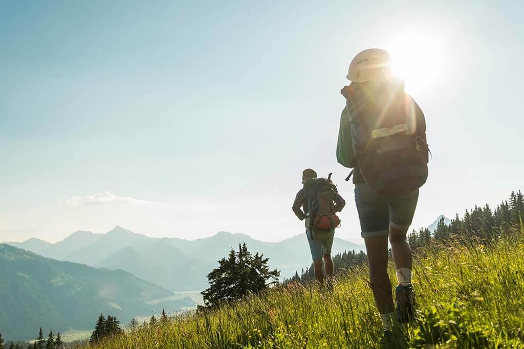 Zwei Personen wandern über eine Wiese in den Bergen.