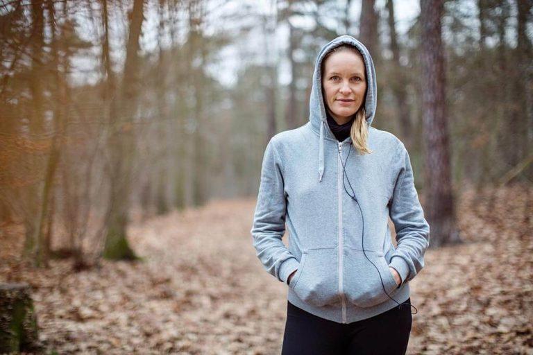 Eine Frau im Pullover steht im Wald und hört Musik.
