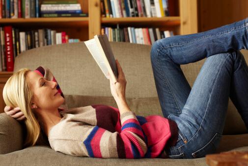 Eine Frau liest ein Buch auf einem Sofa.