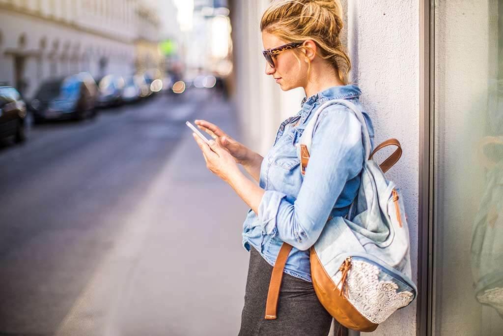 Eine Frau mit Rucksack schaut auf ihr Handy.
