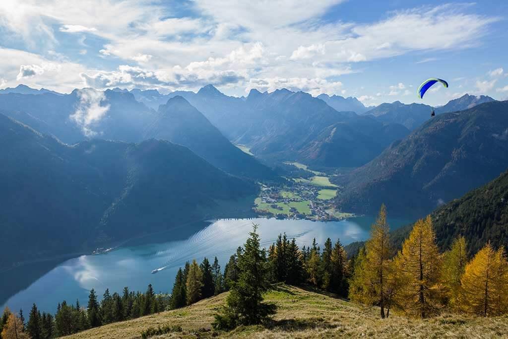 Ein See umrandet von Bergen, in der Ferne sieht man einen Paraglider.