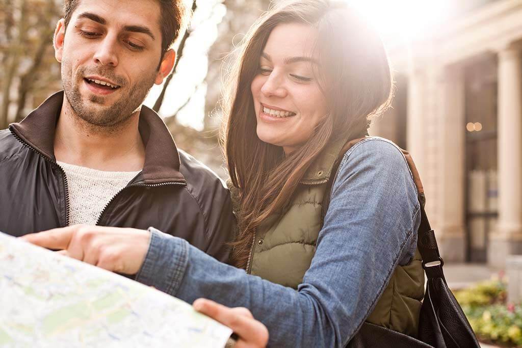 Ein junges Paar schaut zusammen auf eine Landkarte.