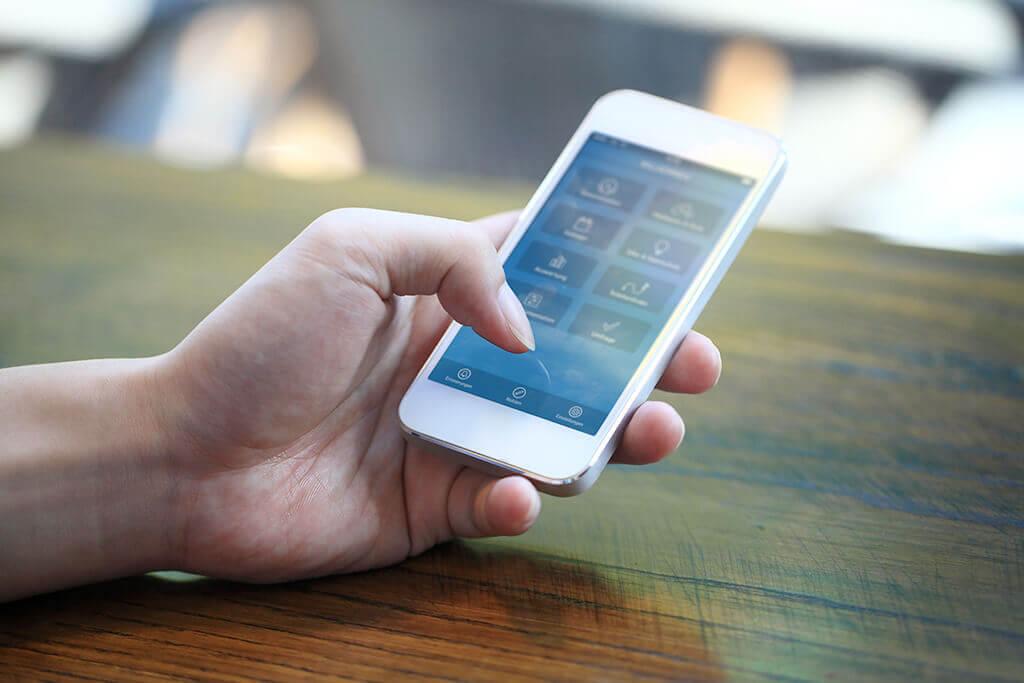 Eine Hand hält ein Smartphone und bedient es.