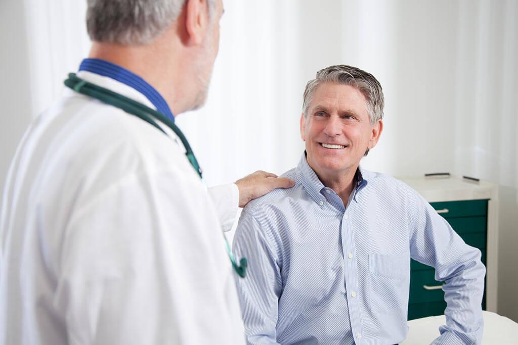 Ein Arzt legt seine Hand auf die Schulter eines Patienten.