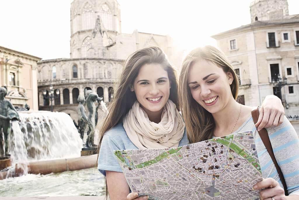 Zwei Frauen stehen vor einem Brunnen und schauen sich zusammen eine Landkarte an.