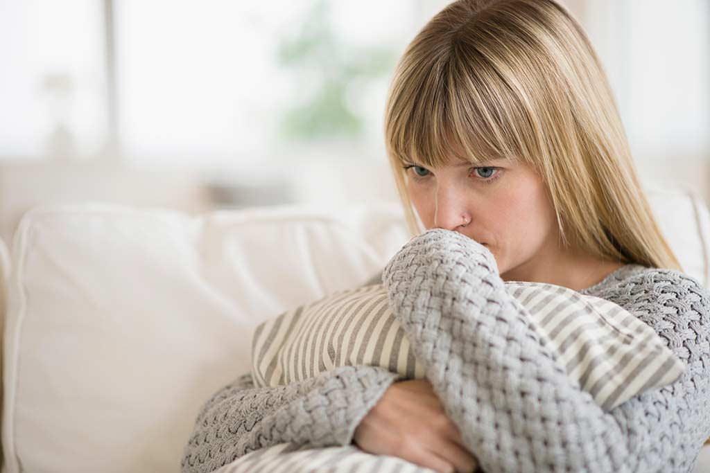 Frau sitzt auf einem Sofa und drückt ein Kissen an sich.
