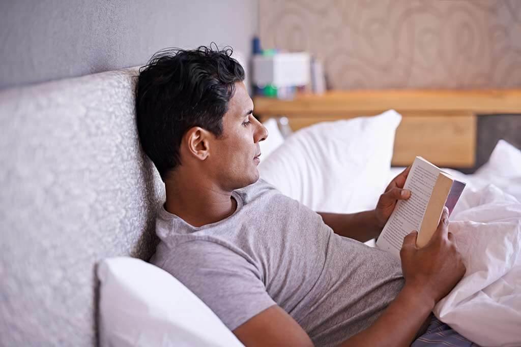 Mann liegt im Bett und liest ein Buch.