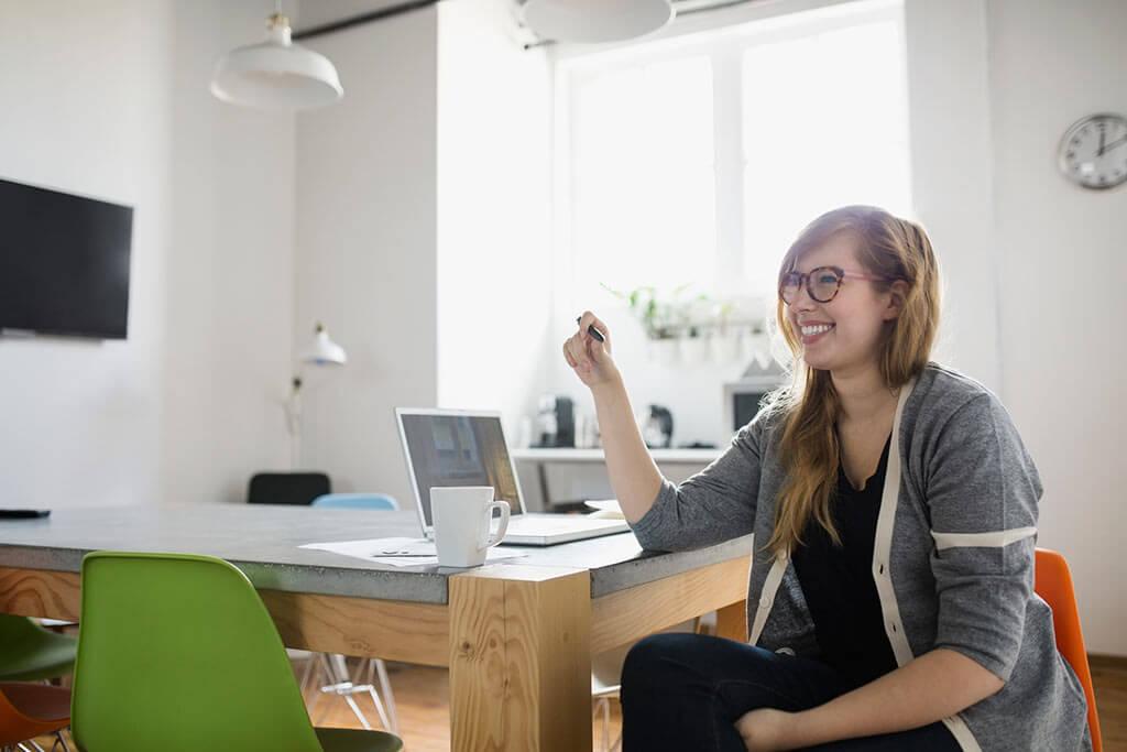 Eine junge Frau sitzt an einem Tisch mit ihrem Laptop und lächelt.