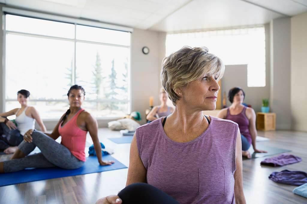 Mehrere Frauen machen Yogaübungen auf Matten.