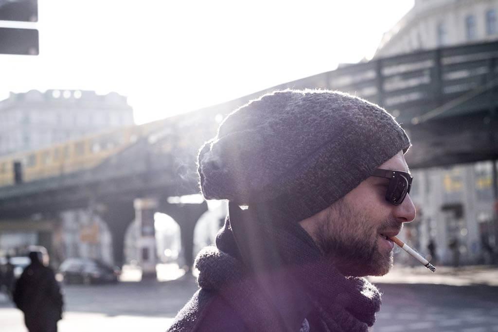 Ein Mann mit Bart trägt eine Wollmütze und eine Sonnenbrille und raucht eine Zigarette.
