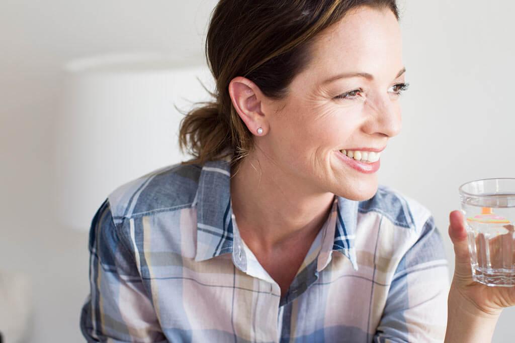 Eine Frau mit einem Glas Wasser in der Hand lächelt.