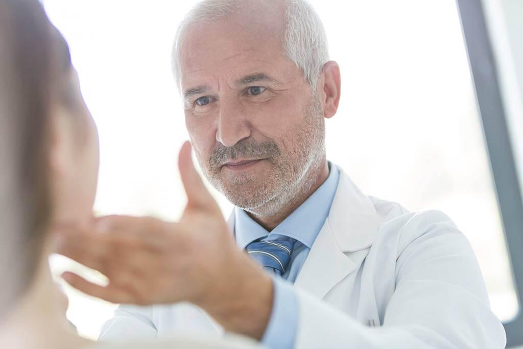 Ein Arzt begutachtet das Gesicht einer Patientin.