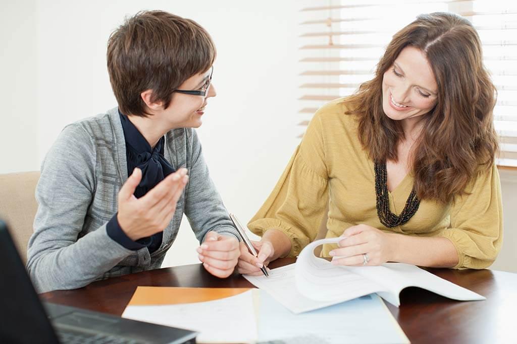 Zwei Frauen sitzen an einem Tisch bei einem Bewerbungsgespräch.