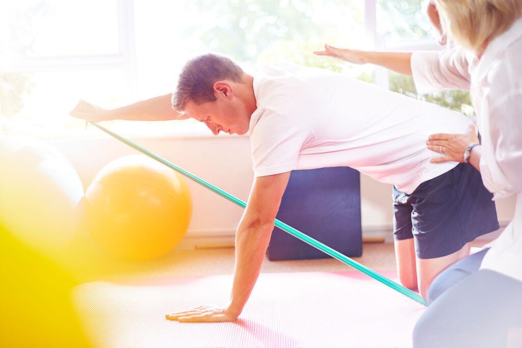Ein Mann macht mti einem Gummiband Gymnastikübungen auf dem Boden.