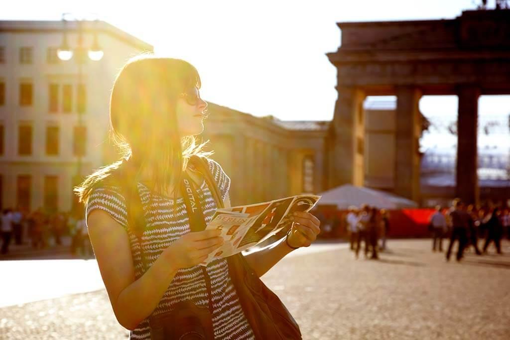 Eine Frau steht mit einem Stadtplan vor dem Brandenburger Tor in in der Sonne.