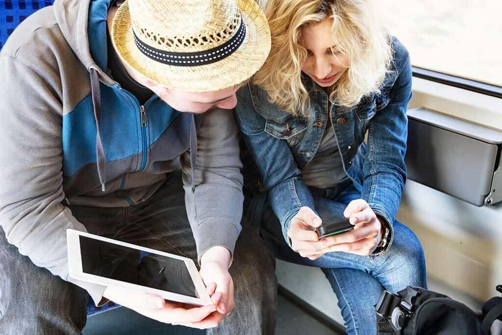 Ein junges Paar schaut zusammen auf ein Handy.