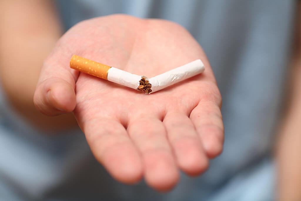 Eine ausgestreckte Hand mit einer zerbrochenen Zigarette.