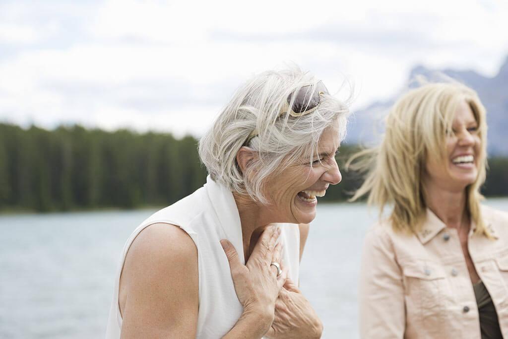 Zwei ältere Frauen lachen zusammen.