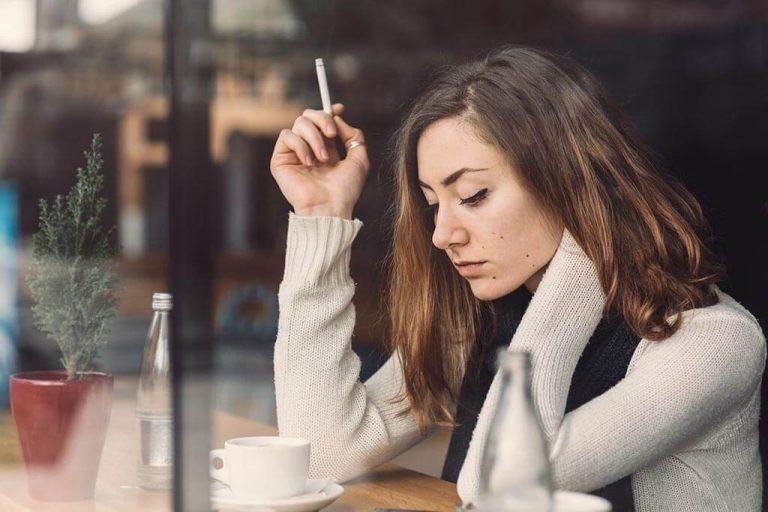 Eine junge Frau mit Zigarette schaut nachdenklich aus dem Fenster.