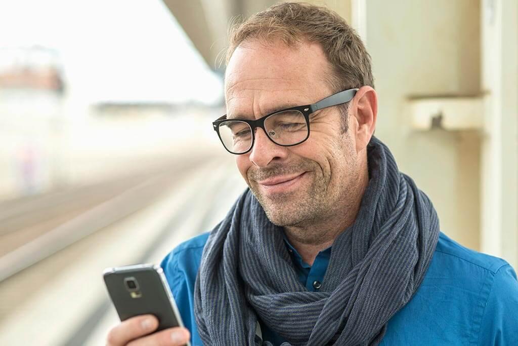Ein Mann schaut lächelnd auf sein Handy.