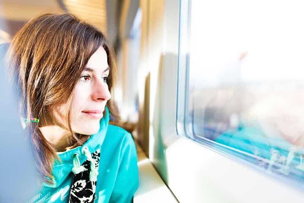Eine junge Frau schaut im Zug aus dem Fenster.