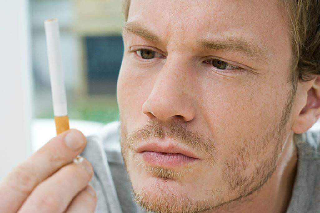 Ein junger Mann schaut nachdenklich eine Zigarette an.