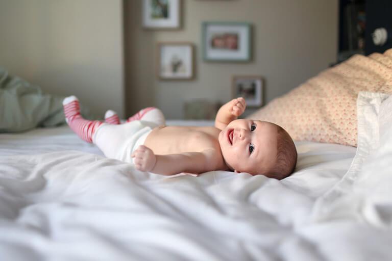 Baby liegt lächelnd auf dem Bett.
