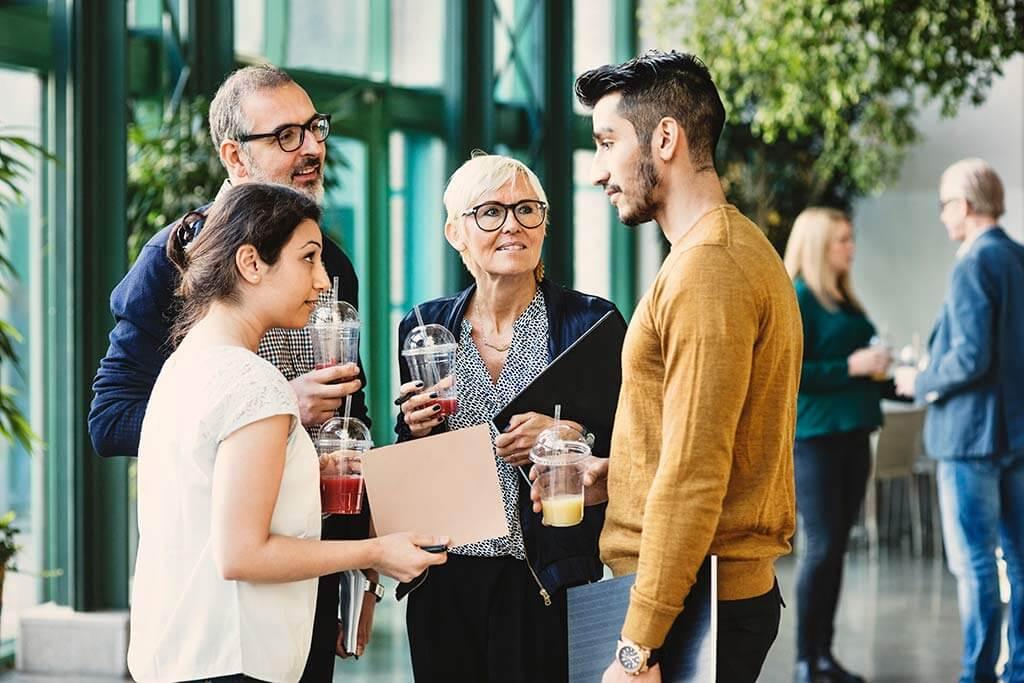 Eine Gruppe Personen unterhalten sich und trinken etwas.